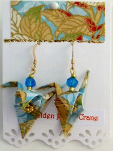 Paper Crane earrings blue background with brown leaves